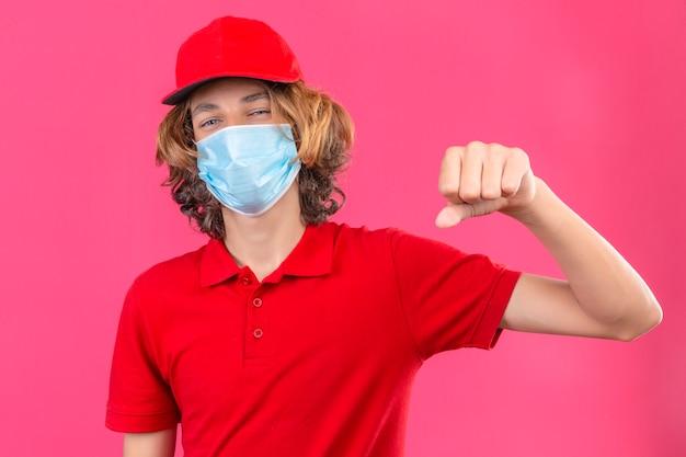 Repartidor joven en uniforme rojo con máscara médica guiñando un ojo gesticulando puño como si saludara aprobando o como señal de respeto sobre fondo rosa aislado