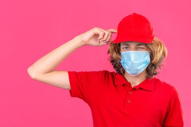Repartidor joven en uniforme rojo y máscara médica guiñando un ojo teniendo dudas mientras se rasca la cabeza de pie sobre fondo rosa aislado