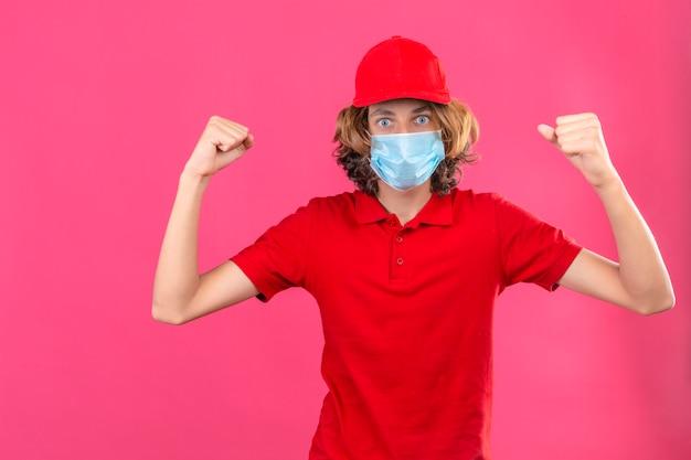 Repartidor joven en uniforme rojo con máscara médica levantando puños orgulloso y seguro concepto ganador de pie sobre fondo rosa aislado