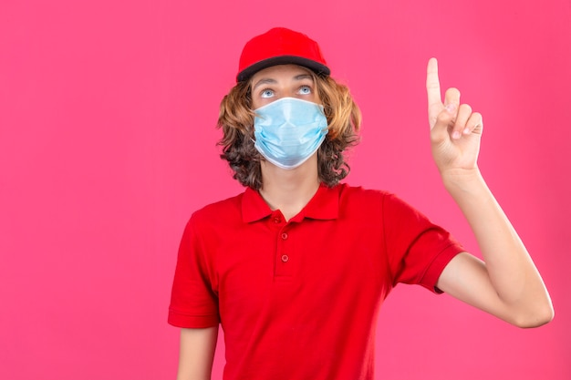 Repartidor joven en uniforme rojo con máscara médica mirando hacia arriba apuntando con el dedo parado sobre fondo rosa aislado