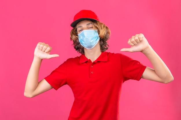 Repartidor joven en uniforme rojo con máscara médica mirando confiado apuntando a sí mismo sobre fondo rosa aislado