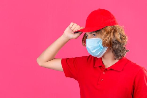 Repartidor joven en uniforme rojo y máscara médica mirando a un lado tocando la tapa con cara seria sobre fondo rosa aislado