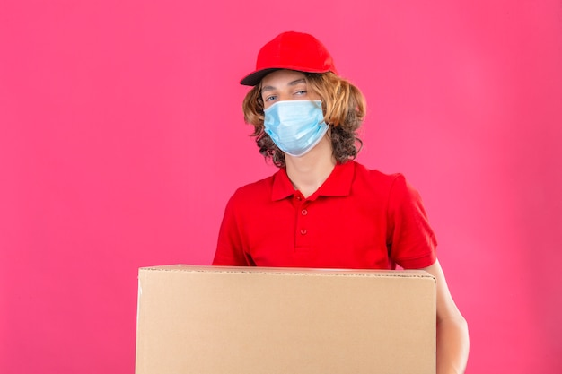 Repartidor joven en uniforme rojo con máscara médica sosteniendo una caja de cartón grande que parece seguro sobre fondo rosa aislado