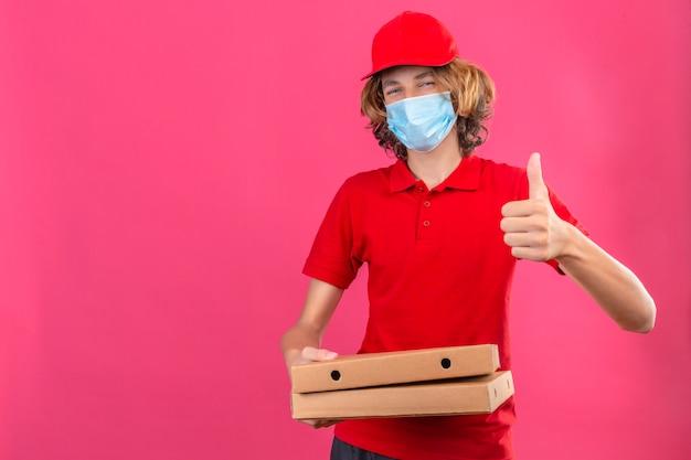 Repartidor joven en uniforme rojo con máscara médica sosteniendo cajas de pizza mirando a la cámara sonriendo alegremente mostrando el pulgar hacia arriba sobre fondo rosa aislado