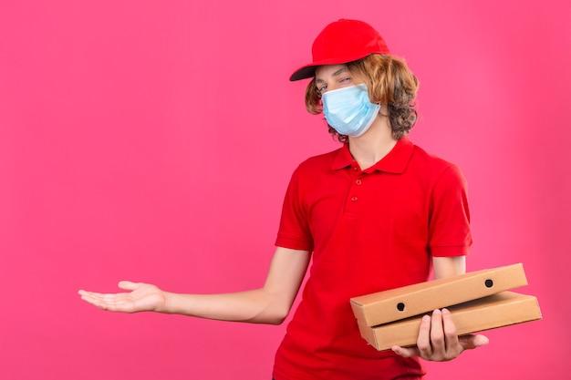 Repartidor joven en uniforme rojo con máscara médica sosteniendo cajas de pizza sonriendo alegre presentando y apuntando con la palma de la mano mirando a la cámara sobre fondo rosa aislado