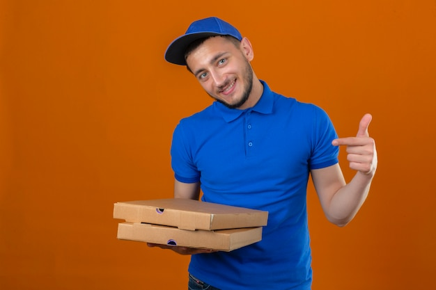Repartidor joven vestido con camisa polo azul y gorra de pie con pila de cajas de pizza mirando a la cámara con una sonrisa en la cara apuntando con el dedo sobre fondo naranja aislado