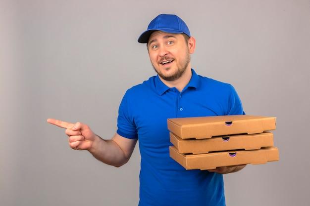 Repartidor joven vestido con camisa polo azul y gorra sosteniendo la pila de cajas de pizza apuntando hacia el lado con el dedo sonriendo alegremente sobre fondo azul aislado
