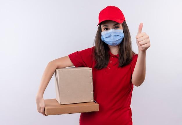 Repartidor joven vistiendo camiseta roja en gorra roja lleva mascarilla sosteniendo una caja y caja de pizza mostrando los pulgares hacia arriba sobre fondo blanco aislado