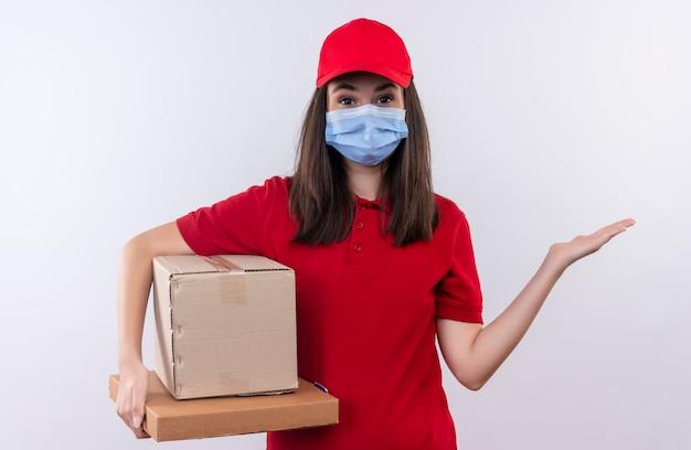 Repartidor joven vistiendo camiseta roja en gorra roja lleva mascarilla sosteniendo una caja y caja de pizza sobre fondo blanco aislado