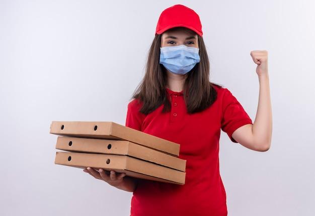 Repartidor joven vistiendo camiseta roja en gorra roja lleva mascarilla sosteniendo caja de pizza sobre fondo blanco aislado