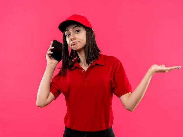 Repartidor joven vistiendo polo rojo y gorra mirando confundido extendiendo el brazo hacia un lado mientras habla por teléfono móvil de pie sobre fondo rosa