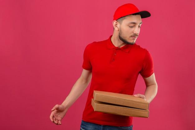 Repartidor joven vistiendo polo rojo y gorra de pie con cajas de pizza mirando a un lado pensando con cara seria sobre antecedentes aislados