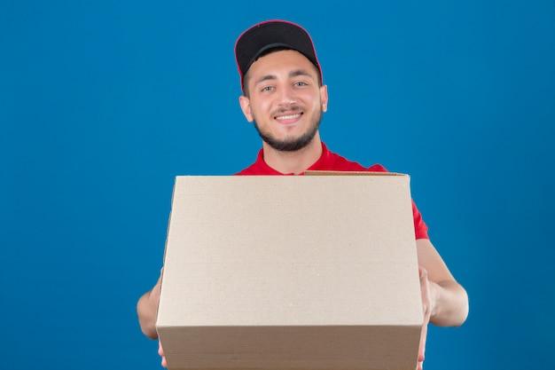 Repartidor joven vistiendo polo rojo y gorra de pie con cartón sonriendo amable mirando a la cámara sobre fondo azul aislado
