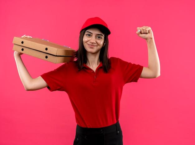 Repartidor joven vistiendo polo rojo y gorra sosteniendo cajas de pizza levantando el puño feliz y positivo sonriente amable de pie sobre fondo rosa