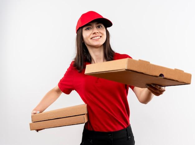 Repartidor joven vistiendo uniforme rojo y gorra sosteniendo cajas de pizza ofreciendo uno de ellos al cliente sonriendo con cara feliz de pie sobre fondo blanco.