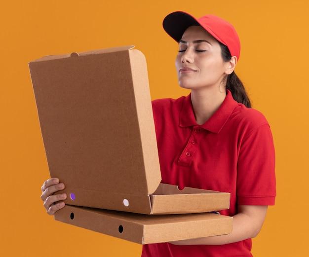 Repartidor joven vistiendo uniforme y tapa abriendo y oliendo caja de pizza aislada en pared naranja