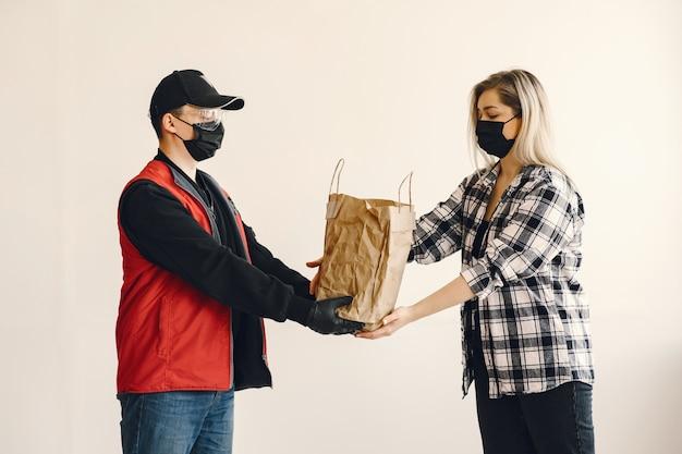 Repartidor en una máscara médica con mujer