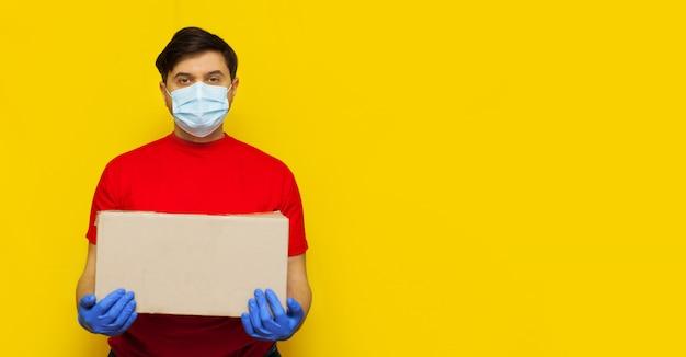 Repartidor en máscara médica sosteniendo un cardbox en pared amarilla