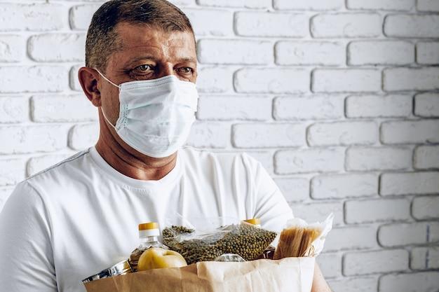 Repartidor en mascarilla y guantes. entrega de alimentos, concepto de compra en línea mientras la pandemia de coronavirus es mundial