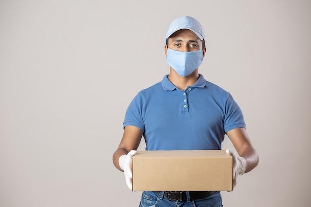 Repartidor mexicano en uniforme protegiéndose con mascarilla y guantes trabajando debido al cierre