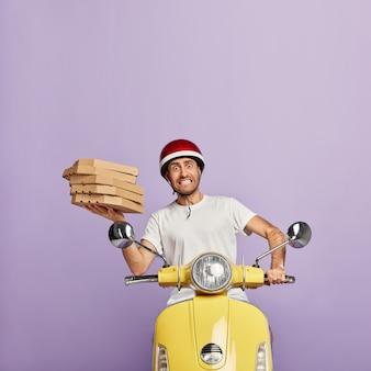 Repartidor ocupado conduciendo scooter amarillo mientras sostiene cajas de pizza