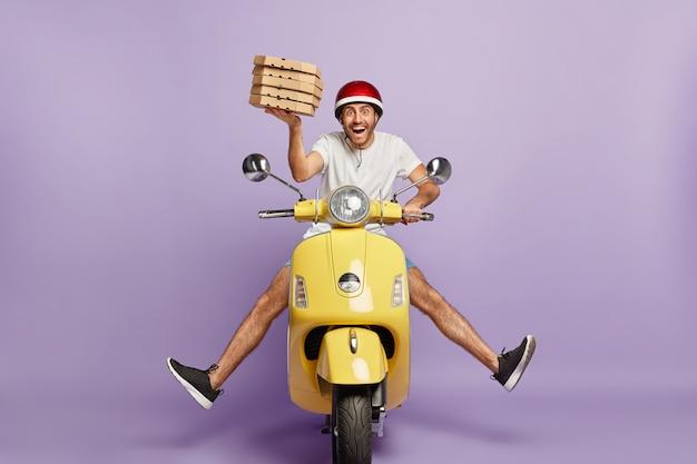Repartidor ocupado conduciendo scooter mientras sostiene cajas de pizza
