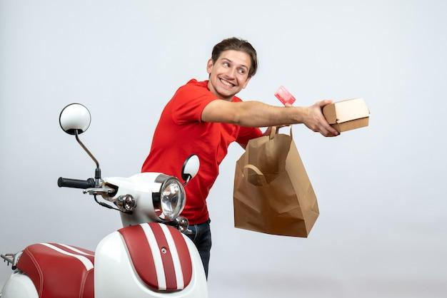Repartidor ocupado en uniforme rojo de pie cerca de scooter y sosteniendo pedidos con tarjeta bancaria sobre fondo blanco.