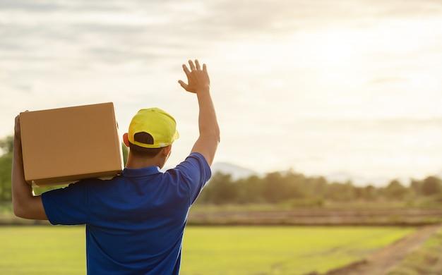 Repartidor con paquete marrón o cajas de cartón entrega al cliente en el campo