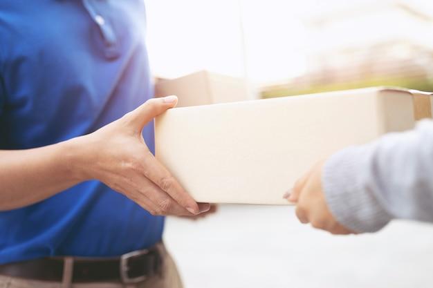 Repartidor de paquetería de un paquete a través de un servicio de envío a domicilio. consign hand cliente de envío que acepta una entrega de cajas del repartidor.