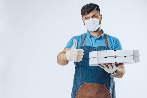 Repartidor de pizza en guantes médicos y máscara. servicio seguro durante el brote de coronavirus covid-19