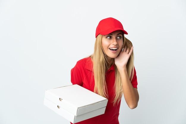 Repartidor de pizza mujer sosteniendo una pizza aislada sobre fondo blanco escuchando algo poniendo la mano en la oreja