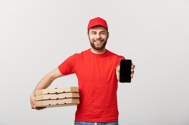 Repartidor de pizza sosteniendo un móvil y cajas de pizza sobre blanco