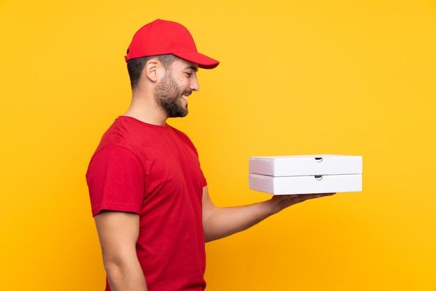 Repartidor de pizza con uniforme de trabajo recogiendo cajas de pizza sobre amarillo aislado con expresión feliz