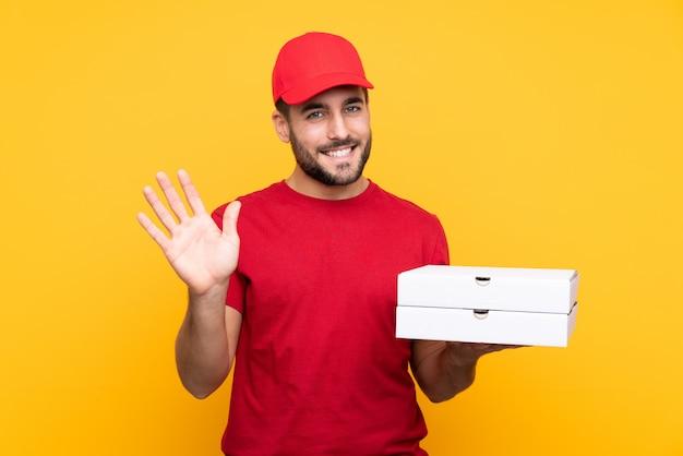 Repartidor de pizza con uniforme de trabajo recogiendo cajas de pizza sobre amarillo aislado saludando con la mano con expresión feliz