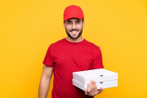 Repartidor de pizza con uniforme de trabajo recogiendo cajas de pizza sobre pared amarilla aislada sonriendo mucho