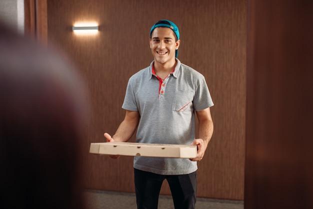 Repartidor de pizzas con caja de cartón en la puerta