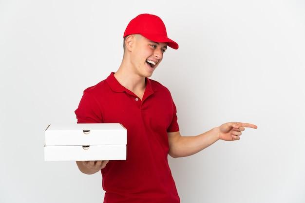 Repartidor de pizzas con uniforme de trabajo recogiendo cajas de pizza aisladas sobre fondo blanco apuntando con el dedo hacia un lado y presentando un producto