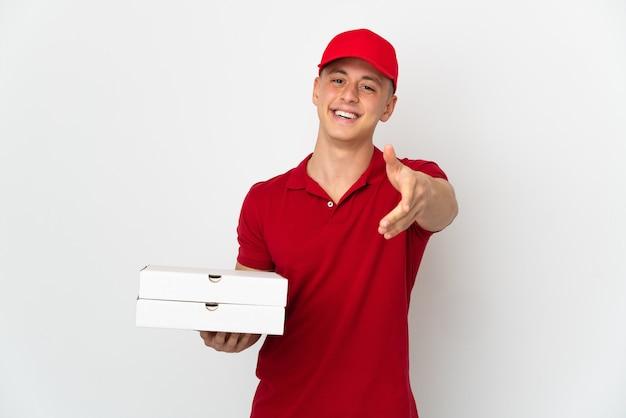 Repartidor de pizzas con uniforme de trabajo recogiendo cajas de pizza aisladas
