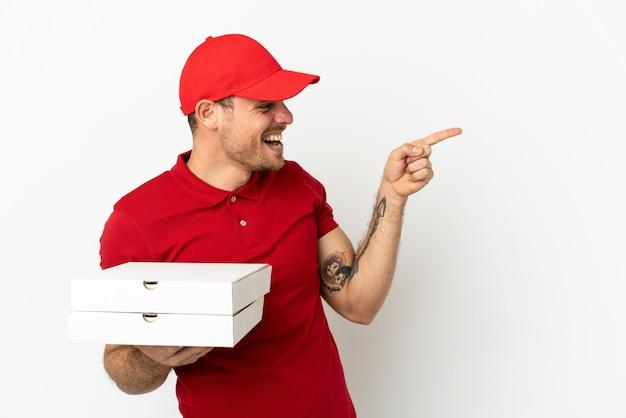 Repartidor de pizzas con uniforme de trabajo recogiendo cajas de pizza sobre una pared blanca aislada apuntando con el dedo hacia un lado y presentando un producto