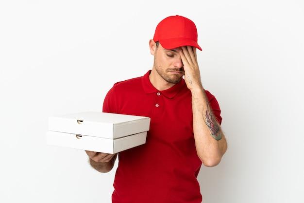 Repartidor de pizzas con uniforme de trabajo recogiendo cajas de pizza sobre una pared blanca aislada con expresión cansada y enferma