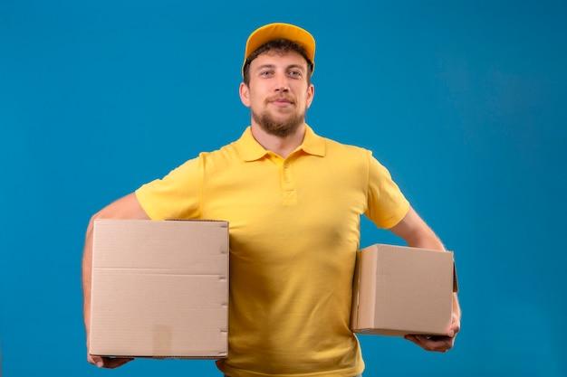 Repartidor en polo amarillo y gorra sosteniendo cajas de cartón mirando confiado de pie en azul