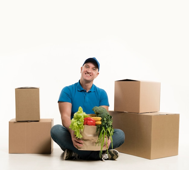 Repartidor posando con bolsa de supermercado y cajas de cartón