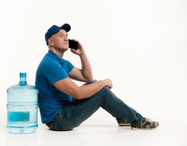 Repartidor posando con botella de agua y teléfono inteligente
