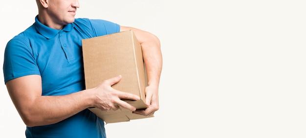 Repartidor posando con caja de cartón en brazos