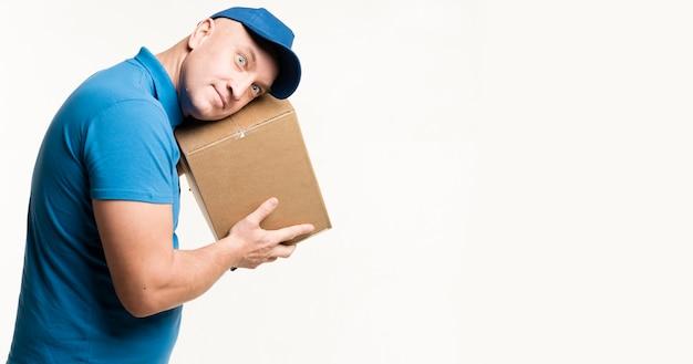 Repartidor posando mientras escucha una caja de cartón