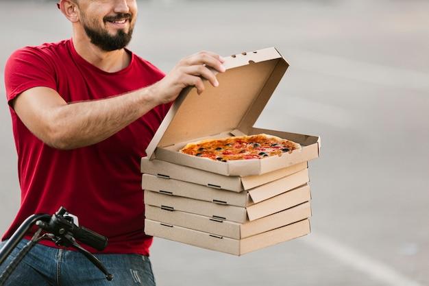Repartidor de primer plano abriendo la caja de pizza
