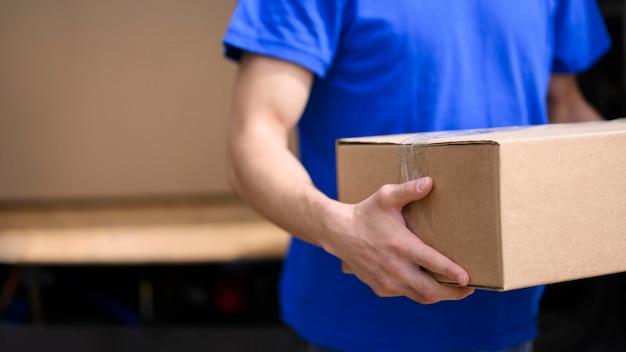 Repartidor de primer plano con caja de cartón