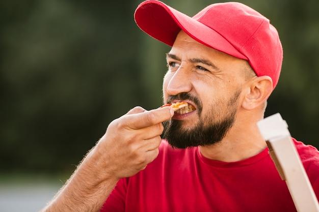Repartidor de primer plano comiendo pizza