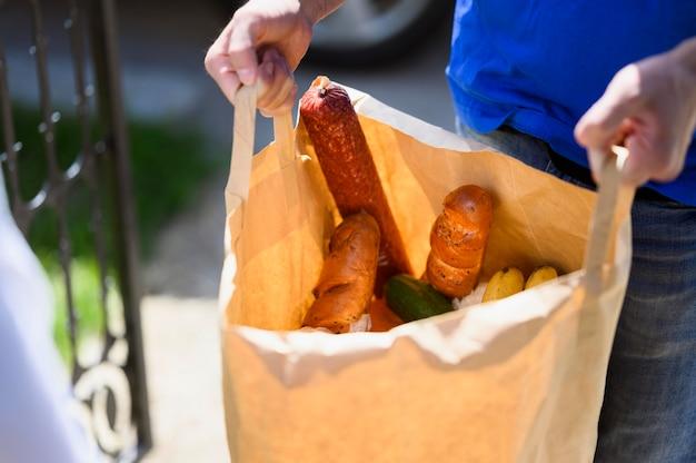 Repartidor de primer plano llevar bolsa con comestibles