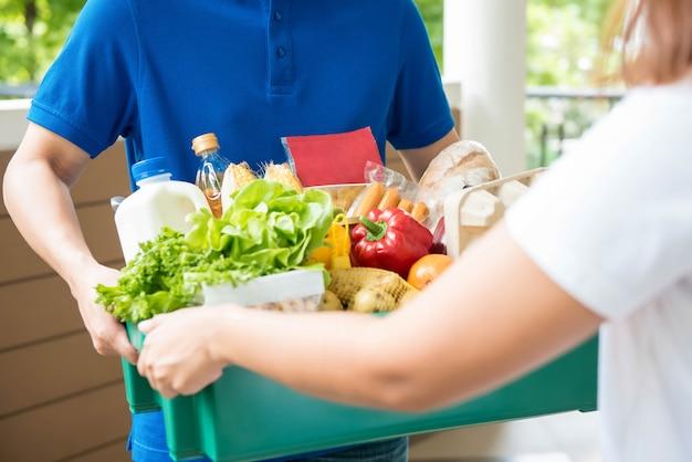 Repartidor de productos agrícolas que entrega comida a una mujer en casa